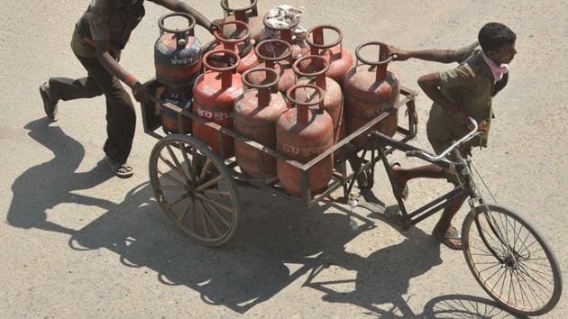 Delivery persons transporting LPG gas cylinders in a rickshaw cart in Patna (Photo by Parwaz Khan / Hindustan Times)