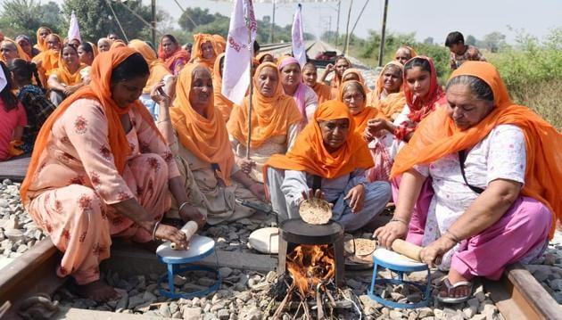 Women making chapatis on traditional stoves on railway track as part of the 'Rail Roko' protest against the new agriculture laws at Devi Dass Pura in Amritsar on Saturday.(Sameer Sehgal/HT)