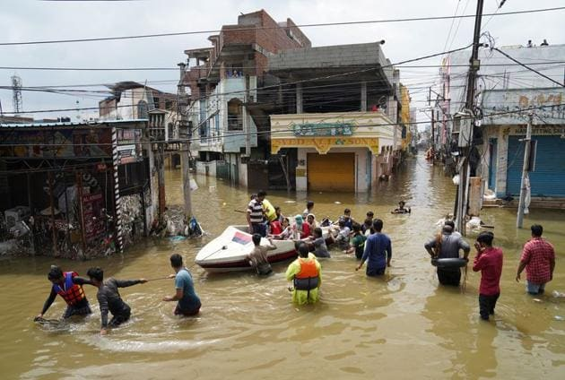 Residents are being evacuated from a flooded neighbourhood after heavy rainfall in Hyderabad on October 15.(Reuters Photo)