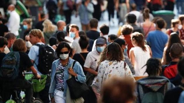 People wearing protective face masks walk in a busy street in Paris, France.(Reuters)