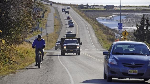 A biker leads a line of cars driving off the Homer Spit at about on October 19, 2020, in Homer, Alaska after a tsunami evacuation order was issued for low-lying areas in Homer.(AP Photo)