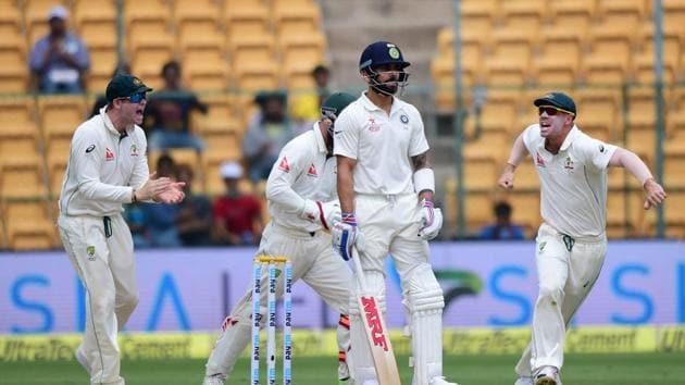 India's Virat Kohli looks on as Australian cricketers celebrate his dismissal during the first day of the second test match at Chinnaswamy Stadium in Bengaluru.(PTI)