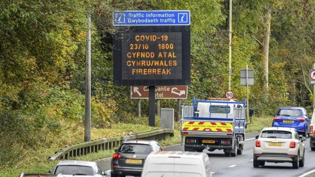 """A matrix sign on the A48(M) heading towards Cardiff informing motorists to Wales entering a """"firebreak"""" lockdown, Friday, Oct. 23, 2020.(AP)"""