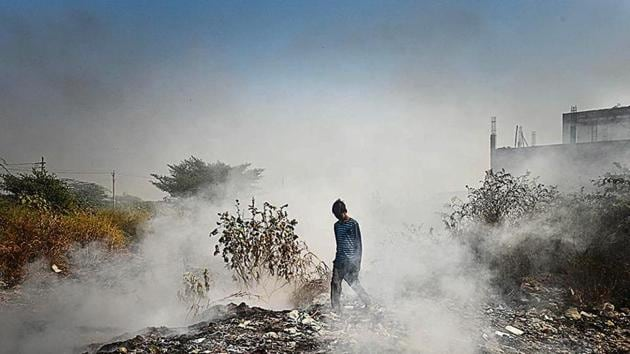 A boy walks through smoke emanating from garbage set on fire in Bhalswa in New Delhi. The national capital reported an AQI of 312, in the 'very poor' category, on Tuesday.