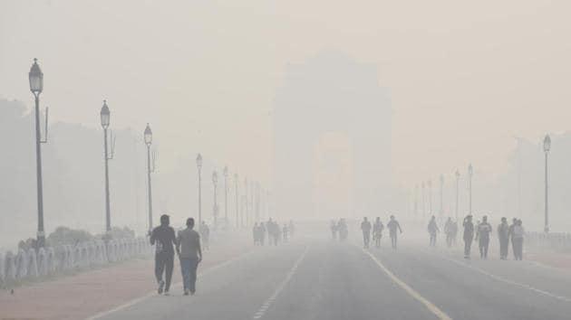Morning walkers at India Gate despite rising air pollution in New Delhi on Thursday.(Arvind Yadav/HT PHOTO)