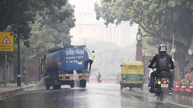 A water tanker spraying water on the road to control dust and pollution at a construction site near Parliament house in New Delhi on Thursday.(Arvind Yadav/HT Photo)