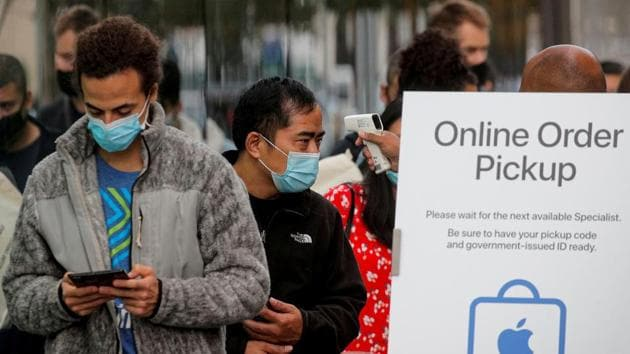 A customer has his temperature taken while in line outside an Apple Store to pick up Apple's new 5G iPhone 12, as the coronavirus disease (Covid-19) outbreak continues in Brooklyn, New York on October 23, 2020.(Reuters File Photo)