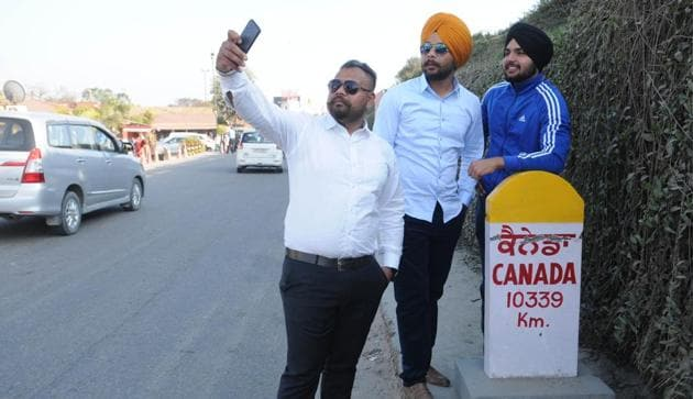 Youngsters taking selfie near a milestone showing the distrance between Canada and Jalandhar, Punjab.(HT file photo)