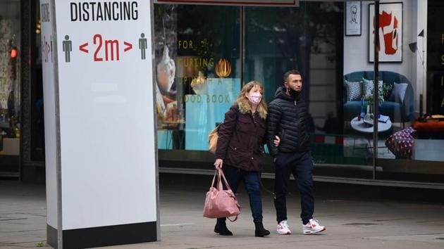 Shoppers with masks on walks past stores and a sign urging people to keep a 2-metre social distance from each other in London on November 1. The new restrictions apply across England, with the other three devolved nations of Scotland, Wales and Northern Ireland already under varying degrees of complete lockdowns. (Justin Tallis / AFP)