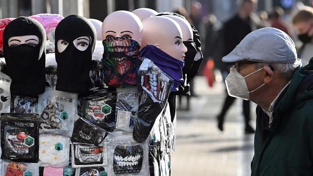 A shopper looks at face coverings displayed for sale in the city centre in Leeds on October 31. Like other European countries, coronavirus cases in the UK began to climb after lockdown measures were eased in the summer and people began to return to workplaces, schools, universities and social life. (Paul Ellis / AFP)