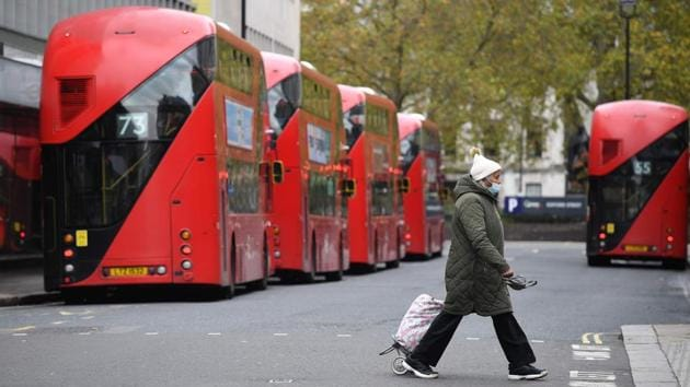 A pedestrian wearing a mask walks past parked buses in London on November 1. The UK recorded 21,915 confirmed coronavirus cases on October 31, taking the total since the pandemic erupted in the country to beyond a million. The country's death toll is up to 46,555. (Justin Tallis / AFP)