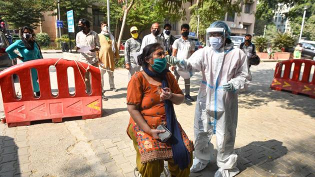 A healthcare worker in PPE coveralls collects a swab sample from a woman for coronavirus testing, at Hari Nagar in New Delhi on Saturday.(Sanchit Khanna/HT Photo)