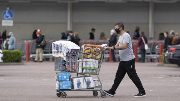 A shopper walks away with a full cart as others queue outside a major supermarket in Leicester on November 1. Prime Minister Johnson had hoped regional restrictions introduced in October would be enough to push the numbers of new infections down. But government scientific advisers predict that on the outbreak's current trajectory, demand for hospital beds will exceed capacity by the first week of December. (Joe Giddens / PA via AP)