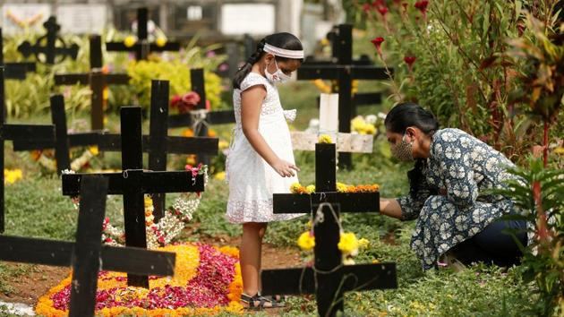 A woman and a child place flowers at a graveyard in Mumbai on November 2. Maharashtra on October 31 reported 74 fatalities due to coronavirus disease (Covid-19), the least deaths reported in a single day in the past 159 days. Before October 31, the state had reported 60 deaths on May 25, HT reported. (Francis Mascarenhas / REUTERS)