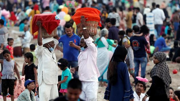 Ice-cream vendors seen interacting at a crowded beach in Mumbai on November 1. Active cases in Maharashtra have fallen steadily and stood at 123,585 on October 31, down from 2.59 lakh a month ago on September 30. (Francis Mascarenhas / REUTERS)