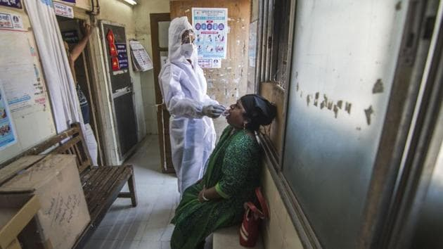 A health worker collects a swab sample from a woman to test for coronavirus infection at Trombay in Mumbai on October 31. Maharashtra's Covid-19 recovery rate had improved to 89.9%, as of October 31. (Pratik Chorge / HT Photo)