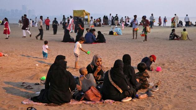 People relax on a beach in Mumbai on October 30. The month-on-month average daily tests being conducted in Maharashtra came down significantly to 70,393 in October from 88,209 in September. (Niharika Kulkarni / REUTERS)