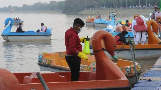 A worker sanitizes a boat at Sukhna Lake in Chandigarh on November 1. India continues to add a considerable tally to the coronavirus caseload, which according to the Union Ministry is a result of the peak of festive season – which has brought people out to the streets in violation of the basic code of Covid-19 safe behaviour. (Keshav Singh / HT Photo)