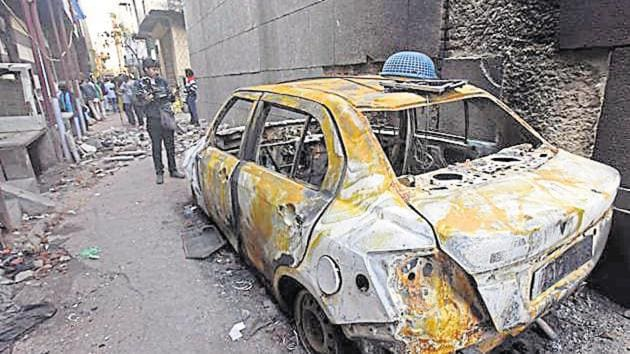 A video journalist stands near a car burnt during last week's violence in north-east Delhi over the Citizenship Amendment Act (CAA), at Shiv Vihar, in New Delhi, India, on Tuesday, March 3, 2020.(Raj K Raj/HT PHOTO)