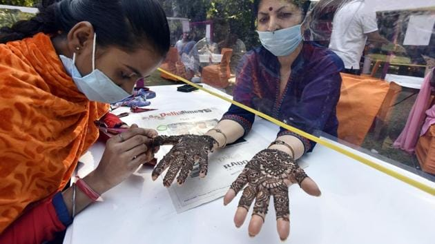 A woman applies henna on the eve of Karva Chauth festival in New Delhi on November 3. Even as active cases lower country-wide, some states such as Manipur, Delhi, Kerala and West Bengal continue to see a surge in caseloads. Delhi recorded 6,725 new single-day cases on November 3, the highest for the capital since the outbreak. (Sanjeev Verma / HT Photo)