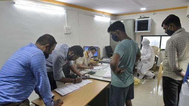 Health care workers collect swab sample of a resident at Goregoan in Mumbai for a Covid-19 test.(HT PHOTO)