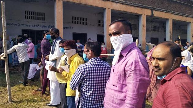 People stand in a queue as they arrive to cast their vote for bypoll in the Ghatampur assembly in Kanpur on Tuesday. (ANI Photo)