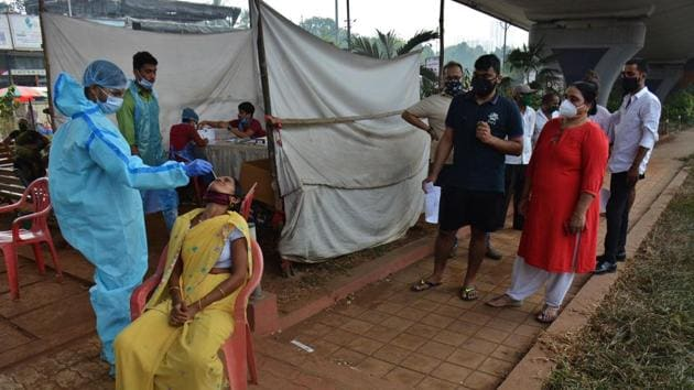 Health care workers collect a swab sample of a resident at a Covid-19 testing Center in Thane on November 2. The active cases of Covid-19 fell below 550,000 on November 3 and the number of recoveries rose to 7,603,121, HT reported from Union health ministry's bulletin. (Praful Gangurde / HT Photo)