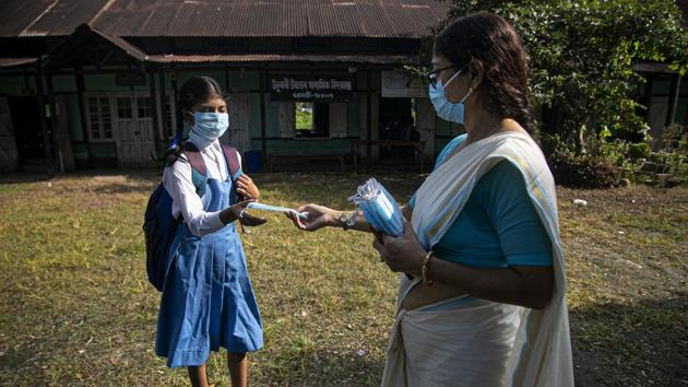 A school principal distributes masks to students as schools in Assam reopen after being closed for months due to coronavirus pandemic in Guwahati on November 2. On November 3, the country also lodged 38,310 fresh infections within 24 hours, the lowest single-day tally seen in the last week. (Anupam Nath / AP)
