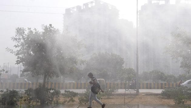 Mist from an anti smog gun deployed at a construction site to tackle pollution fills the air in Greater Noida west, India, on Friday, October 23, 2020.(Photo by Sunil Ghosh / Hindustan Times)