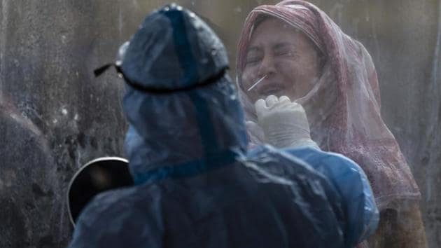 A woman reacts as a health worker takes a nasal swab sample to test for Covid-19 in Srinagar, Kashmir, Wednesday, Nov. 4, 2020.(AP)