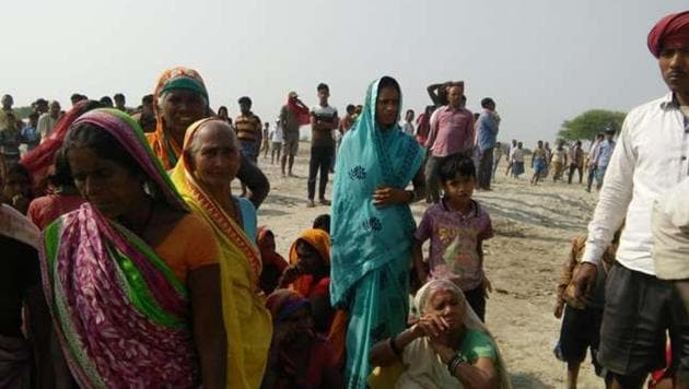Villagers gather near the bank of the Ganga after a boat capsized in the river in Naugachhia on Thursday.(HT PHOTO)