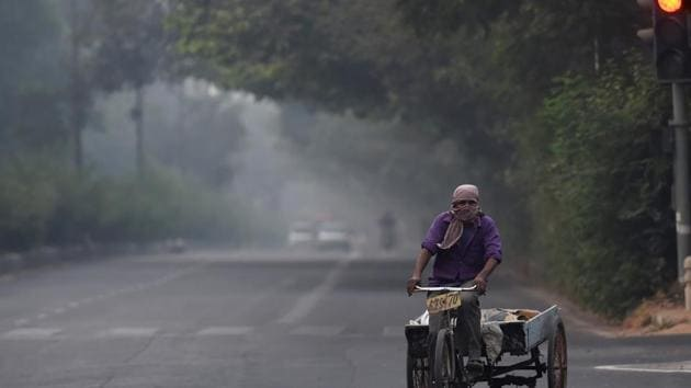 A man pedals his cart amid an atmosphere shrouded in smog, in New Delhi on Thursday.(File photo)