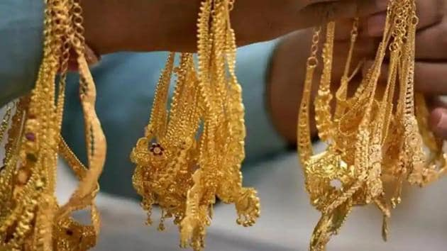 A sales person shows gold ornaments at a jewellery shop, on the occasion of 'Akshaya Tritiya', in Chennai,(PTI File Photo)