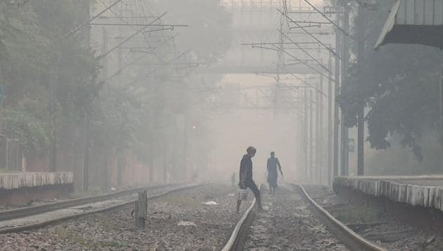 People walk along railway tracks on smoggy morning near Lodhi colony in New Delhi on Friday.(Amal KS/HT PHOTO)