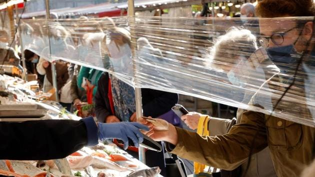 People wearing face masks shop at an open market in Paris on November 4. Owing to a rise in infection that is proving to be deadlier than the first wave, French President Emmanuel Macron put lockdown curbs into effect on October 30, in a second attempt at strongholding the contagion. (Ludovic Marin / AFP)