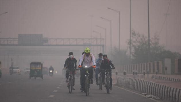 Cyclists ride along NH24 on a smoggy day in New Delhi on November 7. According to the Ministry of Earth Sciences' air quality monitor, SAFAR, Delhi's overall AQI was 443 in the morning on November 7. No quick recovery is expected unless a drastic reduction in fire counts takes place, SAFAR said in its daily bulletin. (Raj K Raj / HT Photo)