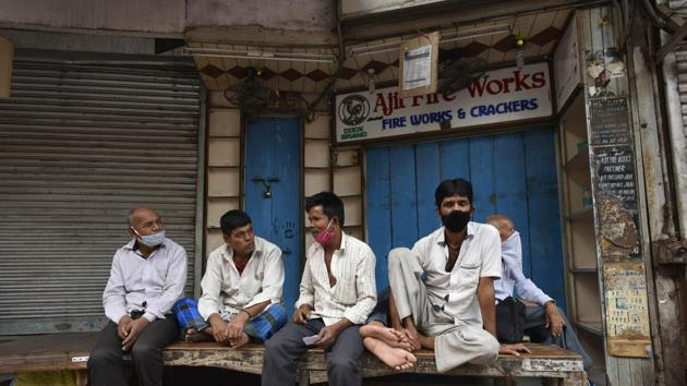 Workers bide time outside a shuttered firecracker shop after the Delhi government banned their sale ahead of Diwali in New Delhi on November 8. Jain also called out people's laxity in adhering to Covid-19 safe behaviour and urged them to treat the mask as the only medicine till a vaccine is available. (Vipin Kumar / HT Photo)