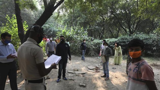 """A police volunteer hands out Covid-19 test results in New Delhi on November 6. Meanwhile, Delhi Health Minister Satyendar Jain said while speaking to the media on November 7 that the national capital had hit the peak of its third wave of Covid-19 and the number of cases suggests it has been the worst so far. He added that """"cases will come down soon."""" (Manish Swarup / AP)"""