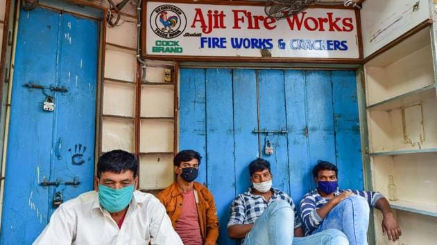 Salesmen sit outside a closed firecrackers shop in Old Delhi, on November 7. The National Green Tribunal (NGT) on November 9 called for a complete ban on the sale and burning of firecrackers in the Delhi-NCR region, to be put into effect from midnight November 9 to November 30. (Kamal Kishore / PTI)