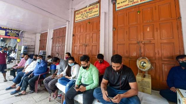 Salespersons sitting outside closed firecracker shops after the implementation of a state government ban on bursting and sale of all kinds of firecrackers from November 7 to November 30, in light of rising air pollution, in Delhi on November 7. (Kamal Kishore / PTI)