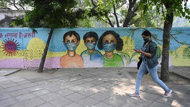 A woman walks past a mural on Covid-19 awareness in New Delhi on November 7. On November 8, Delhi recorded its biggest ever single day jump of 7,745 Covid-19 cases and 77 deaths which pushed the tally and death toll to 438,529 and 6,989 respectively, HT reported. (Sajjad Hussain / AFP)