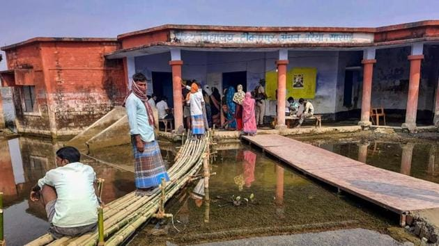 Bihar Election Results 2020: Voters wait at a flooded polling booth in Saran district during Phase 3 polls.(PTI)