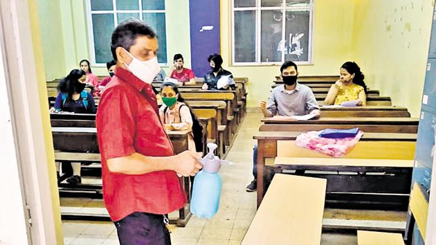 A staffer sanitises the seats and benches at MMK College in Bandra.(HT)
