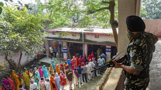 Bihar Results 2020: A security official keeps a vigil as voters stand in queues to cast their votes at a polling station during Bihar Assembly Elections.(PTI file)