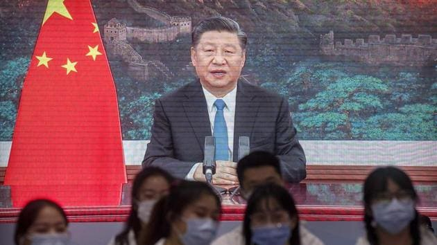 Volunteers watch video screens showing Chinese President Xi Jinping delivering an address to the opening ceremony of the China International Import Expo in Shanghai.(AP)