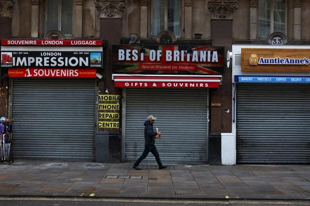 A commuter walks past shuttered stores in London on November 7. Britain accounts for the highest death toll in Europe at around 49,000 as of November 10, and health experts have warned that with a current average of more than 20,000 cases daily, the country will exceed its worst-case scenario of 80,000 deaths, Reuters reported. (Simon Dawson / REUTERS)