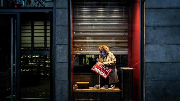 """A shop owner installs a public display board at her shop reading """"For Sale"""" in Lyon, France on November 10. Governments across Europe have been forced to impose control measures including local curfews, closing non-essential shops and restricting movement in a region already facing a wave of job losses and business failures. (Jeff Pachoud / AFP)"""