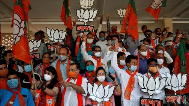 Supporters of Bharatiya Janata Party hold up party symbols and flags as they gather to celebrate the results of the Bihar assembly election on November 10.(REUTERS)