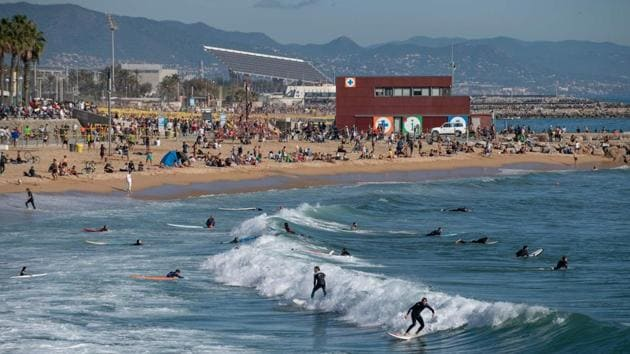 People sunbathe and surf at the Bogatell beach in Barcelona, Spain on November 8. While the new vaccine being developed by Pfizer and BioNTech will take time to arrive, authorities are hoping that once winter is passed, it will stem further outbreaks next year. (Josep Lago / AFP)