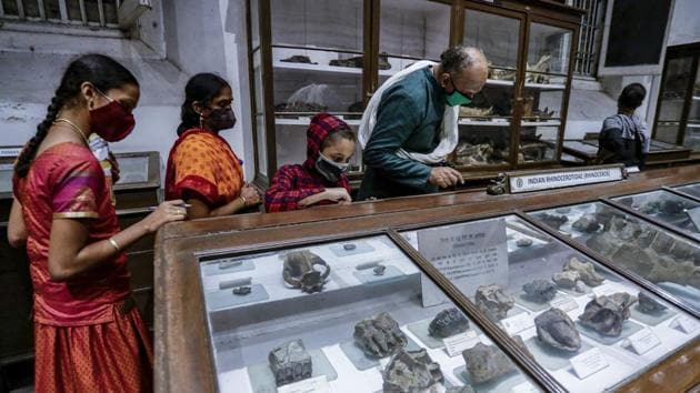 A family looks at exhibits on display at the Indian Museum in Kolkata on November 10. The museum, as well as Science City, another city attraction, were adapting to Covid-19 by restricting the flow of people in halls and also limiting visiting hours, officiating Director of Indian Museum, Kolkata, A D Choudhury told PTI. (Bikas Das / AP)